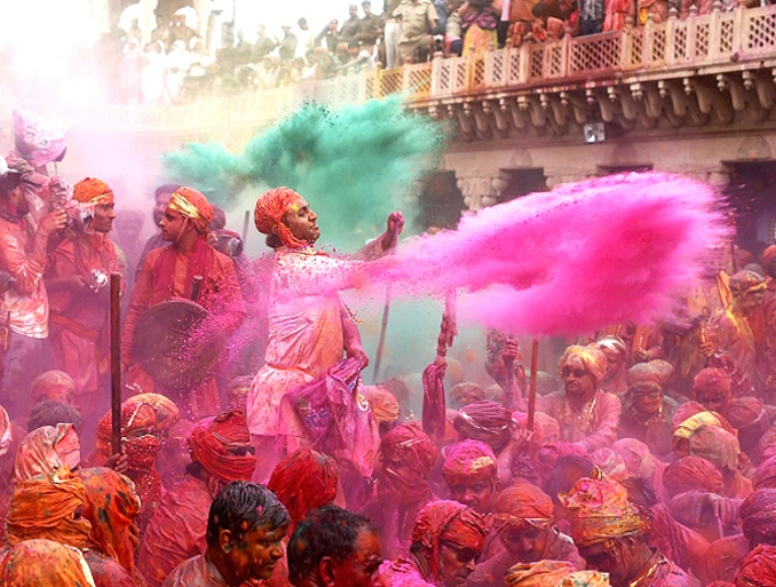 A devotee throws color