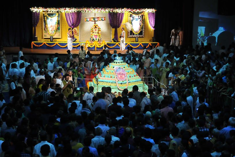 Devotees around Govardhana Cake